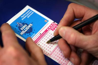 National Lottery Euromillions ticket, hands, pen